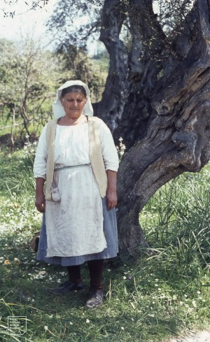 Ypsos woman relaxing from using mattock in vegetable patch and vinyard, 1969