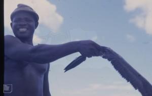 Harry Charles stands astern. Tiller between legs, booby in hand. Aldabra 1970