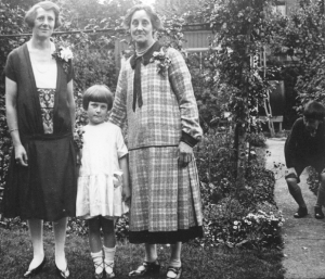 Mary stands between her mother and grandmother, with her brother John, slightly obscured on the right, c. mid 1920s.